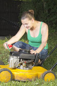 Cute girl oiling and repairing yellow lawn mower — Stock Photo