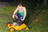 Cute girl repairing yellow lawn mower — Stock Photo