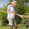 Man removing grass from wooden rake — Stock Photo #11969382