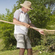 Man removing grass from wooden rake — Stock Photo