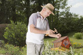 Smilling man fixing old bird house — Stock Photo