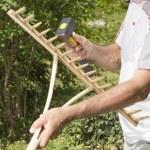 Repairing wooden rake in the garden — Stock Photo