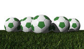 Green soccer balls on a green grass — Stock Photo