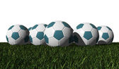 Cyan soccer balls on a green grass — Stock Photo