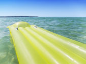 Yellow airbed in the sea — Stock Photo