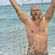 Portrait of man with spashes in the sea — Stock Photo