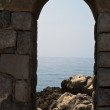 Стоковое фото: Old arch with seand rocks in Cefalu
