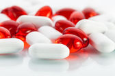 Vitamin pills: Red capsules and white tabs — Stock Photo