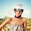 Sexy brunette woman with sunglasses, hat and floral pattern dress — Stock Photo #10807870