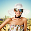 Sexy brunette woman with sunglasses, hat and floral pattern dress — Stock Photo