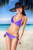 Sexy brunette posing in a purple swimsuit — Stock Photo