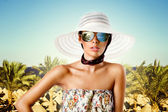 Sexy brunette woman with sunglasses, hat and floral pattern dress — Stockfoto
