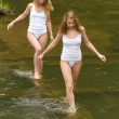 Two girls in white t-shirts are on the green water. — Stock Photo #11255731
