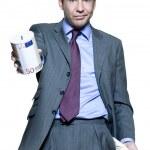 Portrait of businessman holding money box and showing empty pocket — Stock Photo