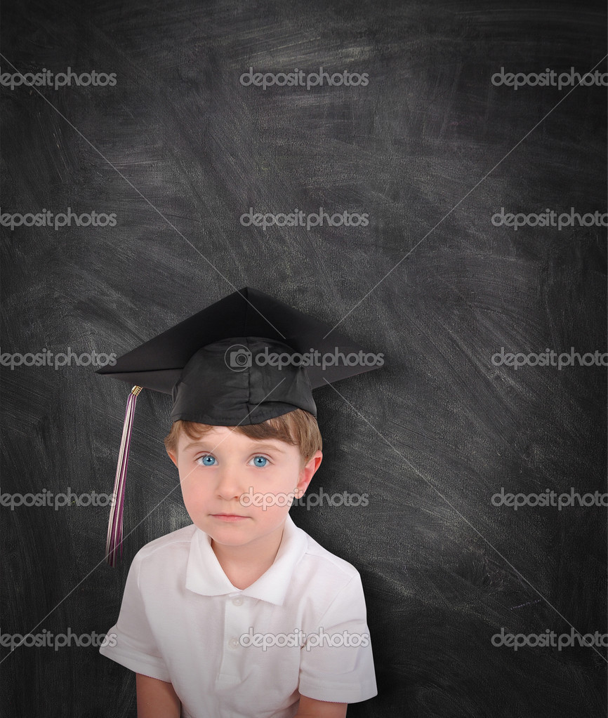 A young boy is wearing a graduation cap and tassel against a black chalk board. Add your text to the copyspace. Use it for an education or school concept. — Stock Photo #10895242