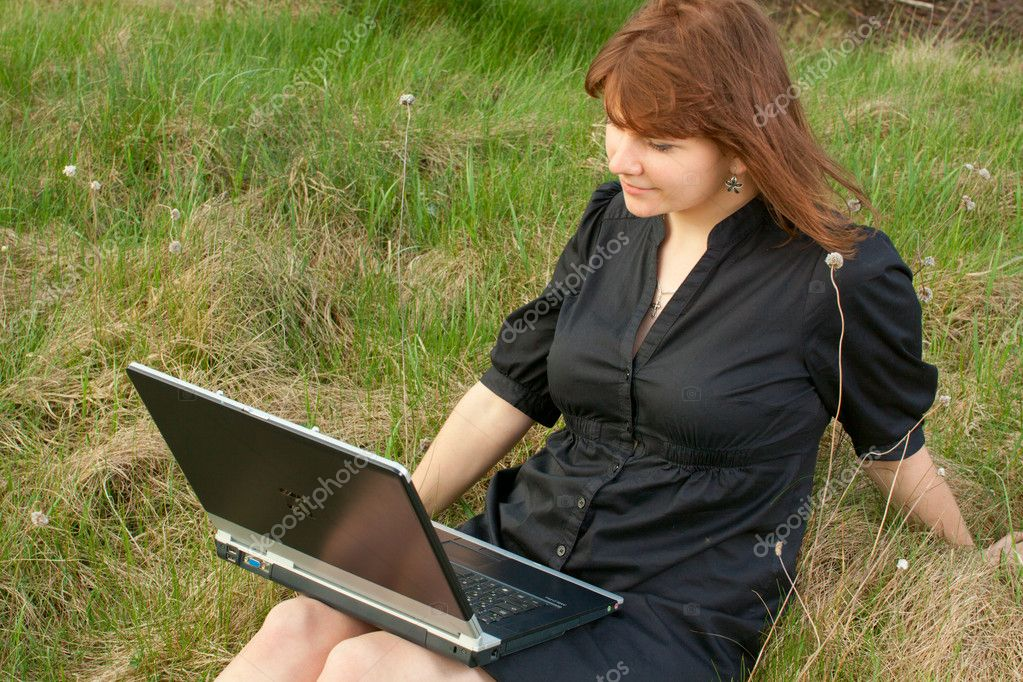 Girl with laptop in black dress sitting on grass, — Stock Photo #10740304