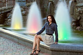 Beautiful young woman over the fountain — Stock Photo