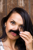 A funny brunette girl with moustache — Stock Photo
