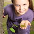 Stock Photo: Girl shows green shoot of tree