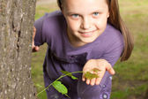 Girl shows green shoot of tree — Stock Photo