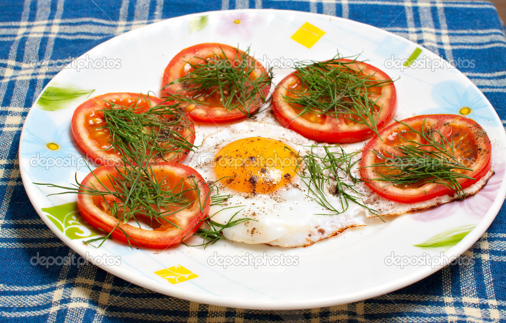 Plate with fried egg and tomatoes on the tablecloth — Stock Photo #11381018