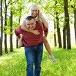 Man giving piggyback ride to woman — Stock Photo