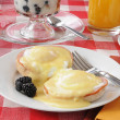 Eggs benedict with fruit cocktail — Stock Photo