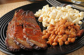 Closeup up of beef brisket with baked beans — Stock Photo