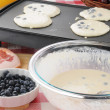 Pancakes cooking on the griddle - Stock Photo