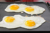 Eggs frying on the griddle — Stock Photo