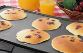 Blueberry pancakes on the grill — Stock Photo