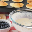 Blueberry pancakes cooking on the grill - Stock Photo