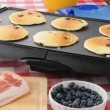 Stock Photo: Hotcakes cooking on griddle