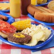 A hamburger on a picnic table loaded with food - Stock Photo