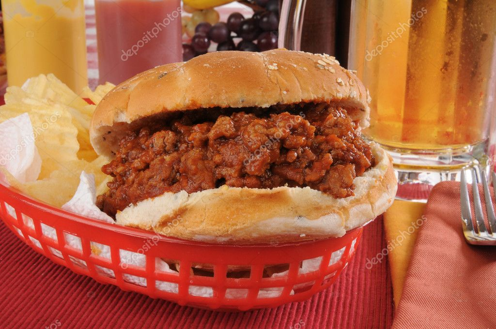 A Sloppy Joe in a basket with a mug of beer — Stock Photo #11978766