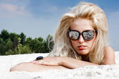 Beautiful blond woman in sunglasses in the sand — Stock Photo