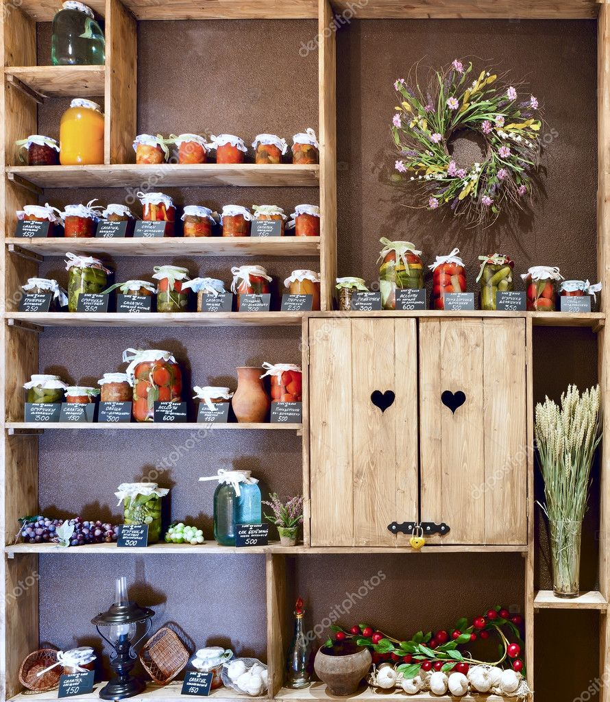Domestic stocks with pickled vegetables in glass jars on wooden shelves    #11036359