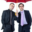 Two businessmen standing under an umbrella — Stock Photo