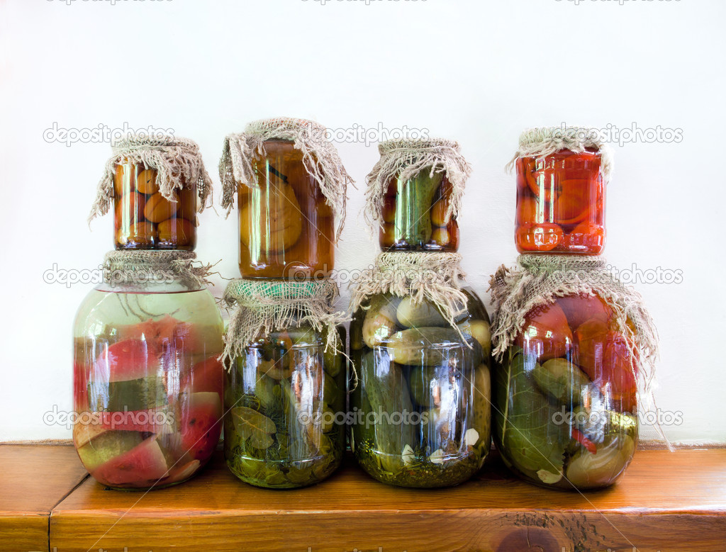 Pickled vegetables in glass jars on a wooden shelf  Stock Photo #11725599