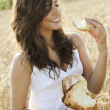 Smiling girl eats piece of bread — Stock Photo #11485212