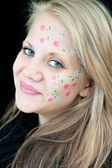 Cute girl with a flowery face painting — Stock Photo