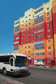 Bus and multi-coloured building — Stock Photo