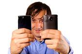 Businessman holding mobiles — Stock Photo