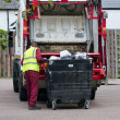 Bin man collecting the rubbish from a large bin - Stock Photo