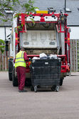 Bin man collecting the rubbish from a large bin — Stock Photo