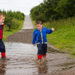 Little boy splashing in a puddle — Stock Photo #11682125