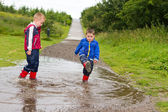 Little boy splashing in a puddle — Stock Photo