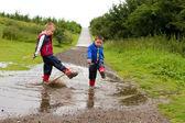 Little boy splashing in a puddle — Stock Photo