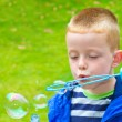 Boy blowing bubbles — Stock Photo