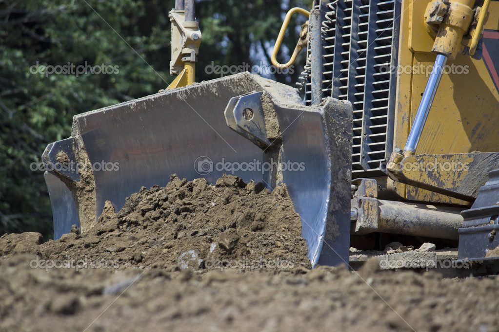 A bulldozer driving over dirt — Stock Photo #12074857